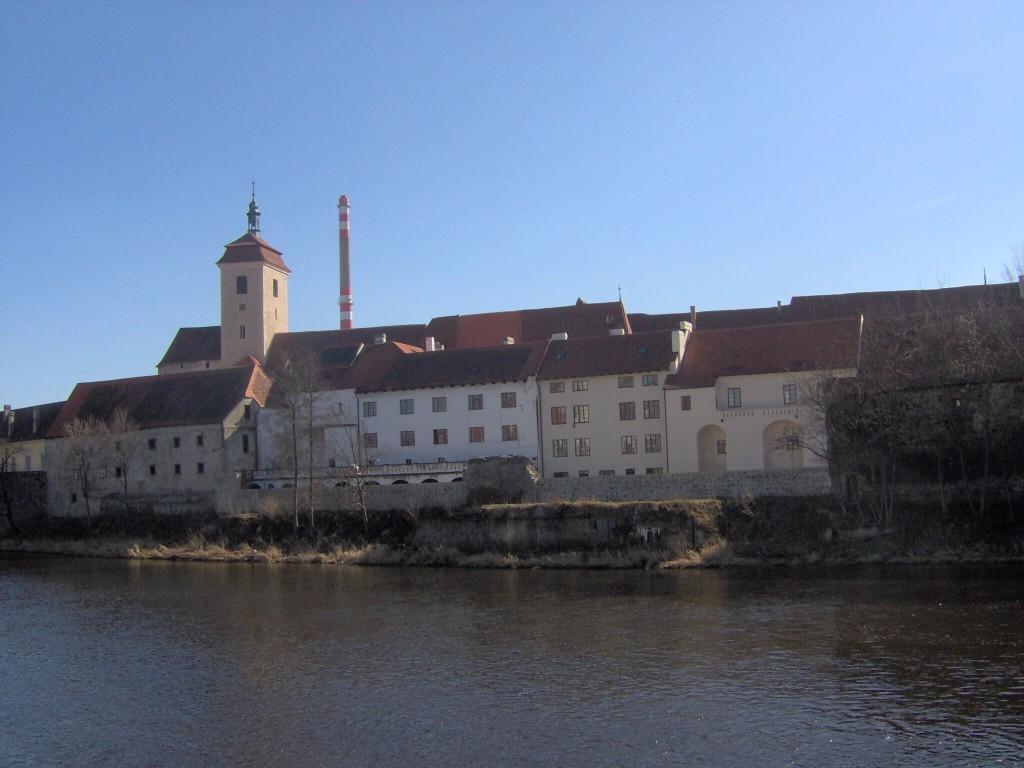 Pohled na hrad od řeky, teplárenský komín v pozadí