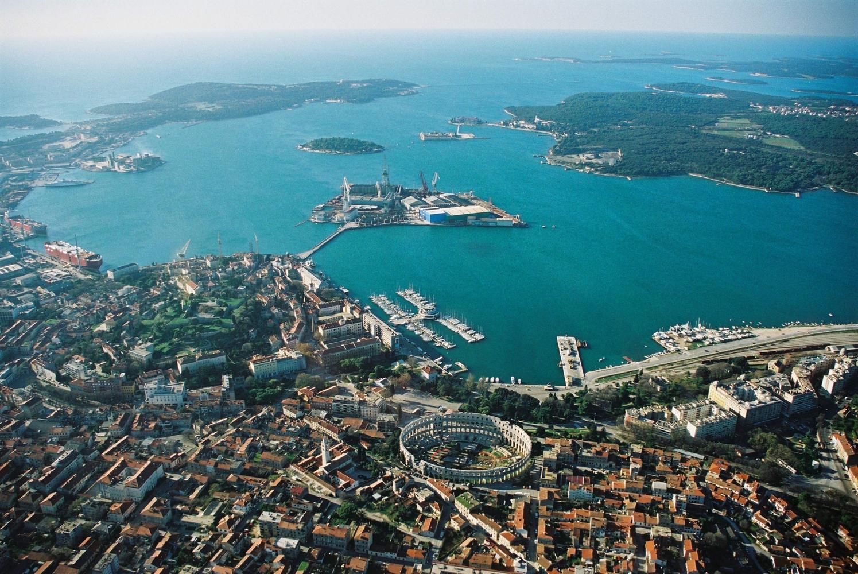 Letecký pohled na město Pula, lze vidět staré město i moře s malými ostrůvky, na horizontu je vidět zakřivení Zeměkoule