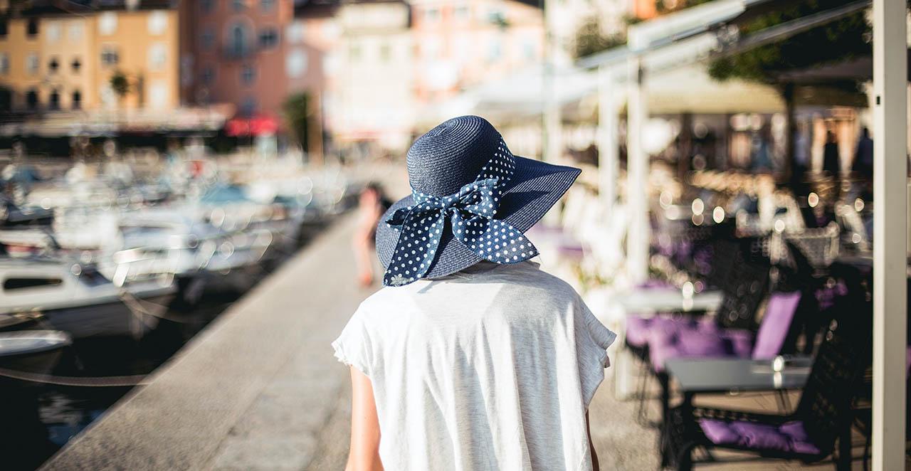 Dívka v modrém klobouku na chorvatské riviéře, pozadí je rozmazané