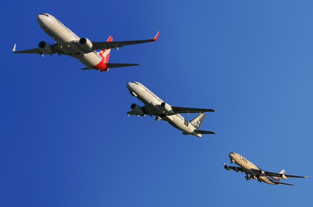 Tři velká dopravní letadla v řadě na modré obloze