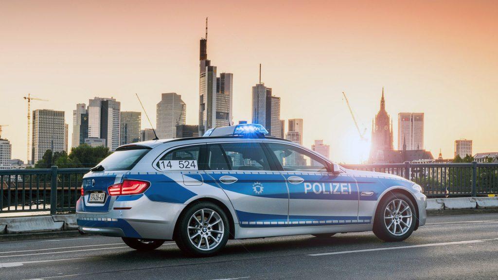 policejní auto na dálnici, v pozadí mrakodrapy